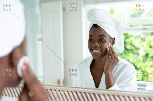 African American woman in bathrobe removing makeup while looking in the mirror at bathroom. staying at home in self isolation in quarantine lockdown