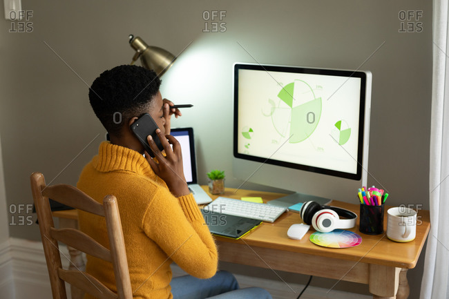 African American woman talking on smartphone and using computer while working from home. staying at home in self isolation in quarantine lockdown