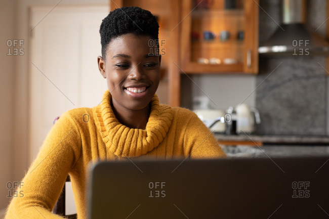 African American woman wearing using laptop and smiling in kitchen. staying at home in self isolation during quarantine lockdown.