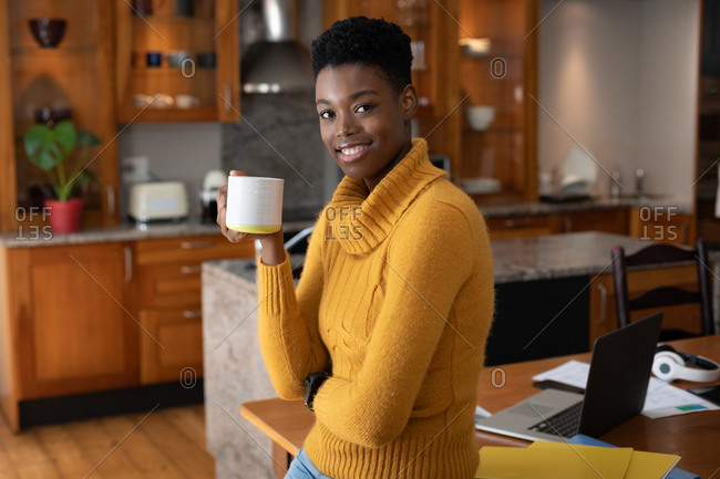African American woman standing in kitchen drinking coffee looking at the camera and smiling. staying at home in self isolation during quarantine lockdown.