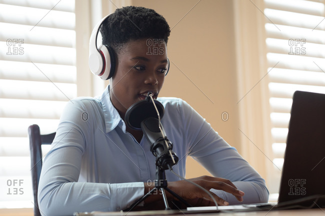African American woman wearing headphones using microphone and laptop. communication online, staying at home in self isolation during quarantine lockdown.