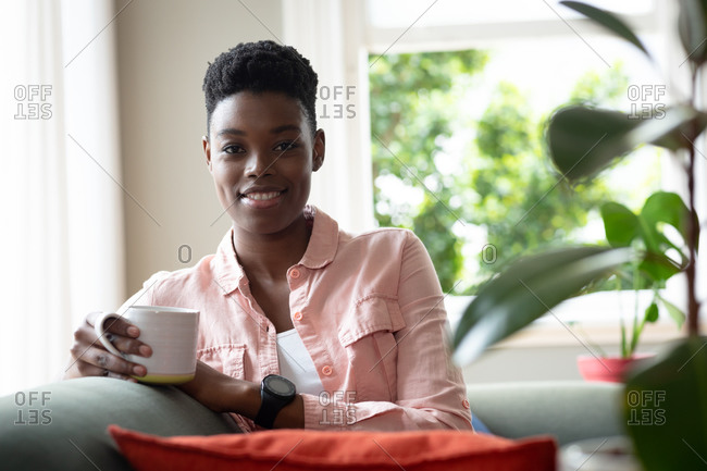 Portrait of African American woman sitting on couch drinking coffee looking at camera and smiling. staying at home in self isolation during quarantine lockdown.