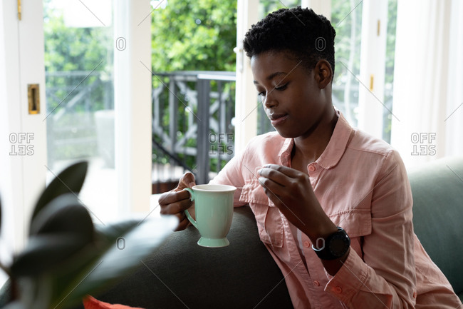 African American woman sitting on couch drinking coffee. staying at home in self isolation during quarantine lockdown.