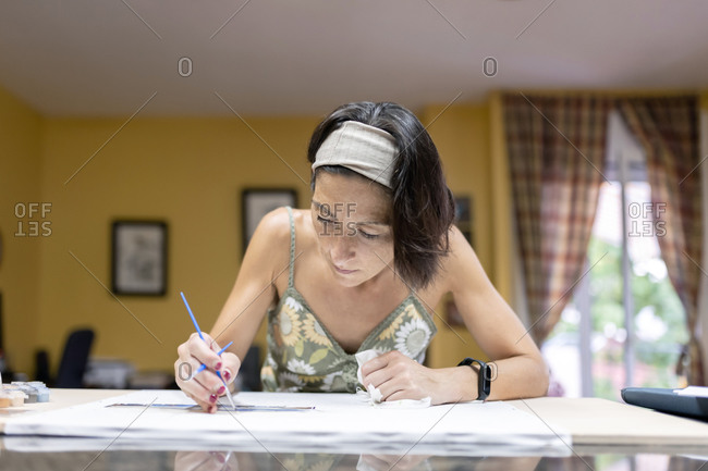 Artist woman in headband painting behind work desk with a brush.