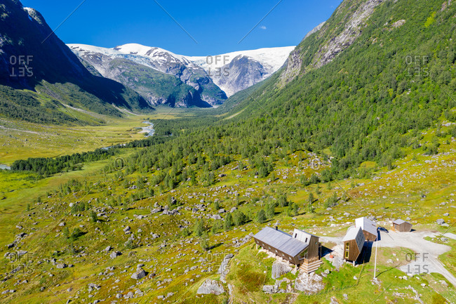 TUNGESTOLEN, NORWAY - 26-AUGUST-2020: Aerial view of tourist cabin Tungestolen at the glacier Jostedalsbre, valley Langedalen in the back,  Sognefjord region, Norway.