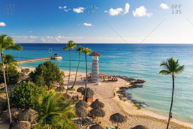 November 3, 2019: Aerial view of palms and tourists enjoying the beach in the golden hour, Bayahibe, La Romana, Dominican Republic