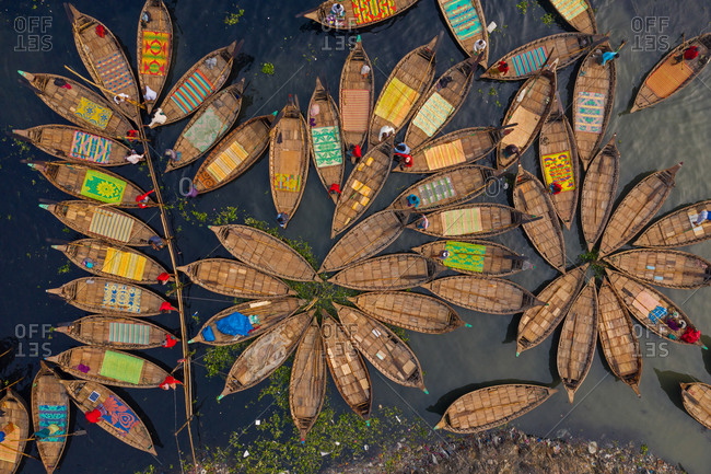 Aerial view of Hundreds of wooden boats fan out around their moorings in patterns which resemble flower in Buriganga river, Dhaka, Bangladesh.