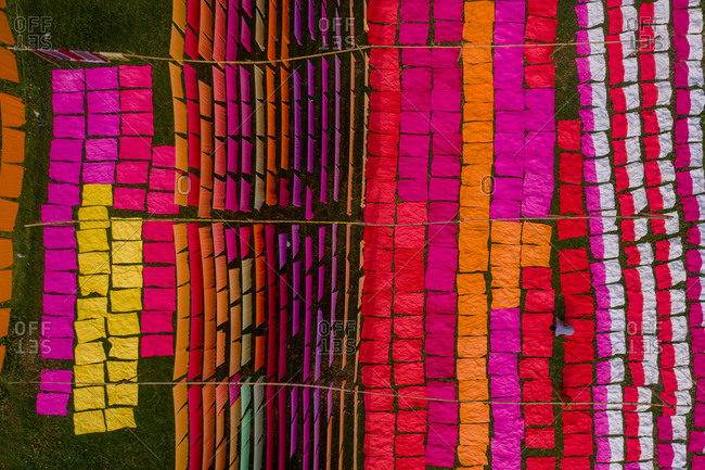 Aerial view of hundreds of sheets of multicolored cloth drying under sunlight in Narayanganj, Bangladesh.