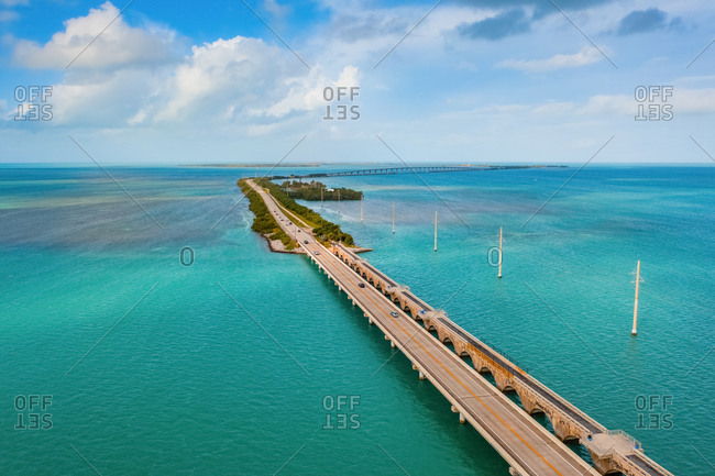 Aerial view of vehicles passing the Highway Piers Historical Marker on a sunny day, Islamorada, FL, United States