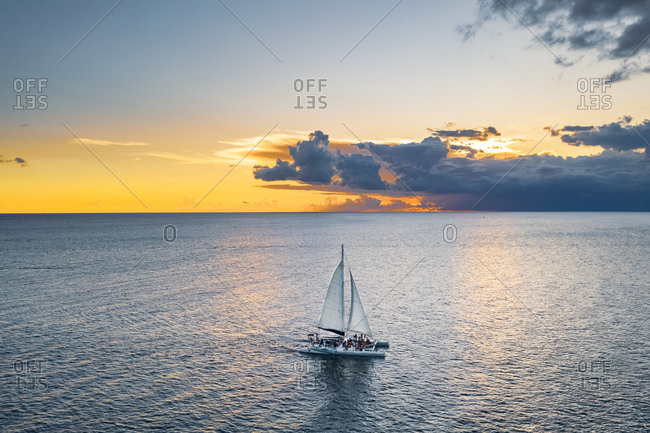 Aerial view of catamaran boat full of people sailing under an orange sunset, La Altagracia, Dominican Republic