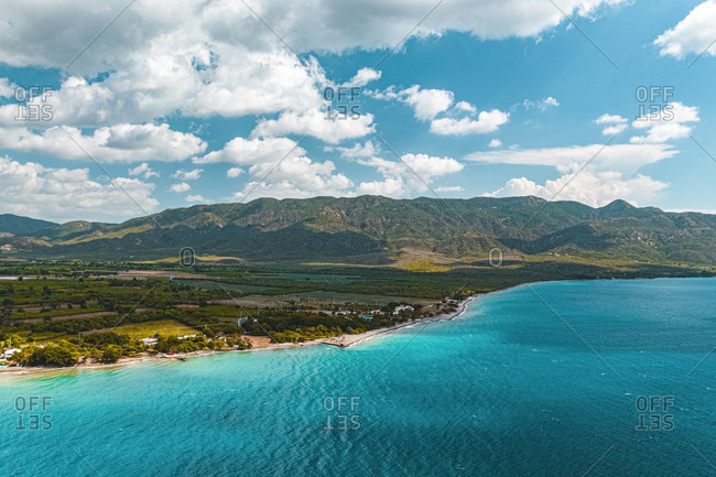 Aerial view of the coastline near the green mountains in a cloudy day, Ocoa, Azua, Dominican Republic
