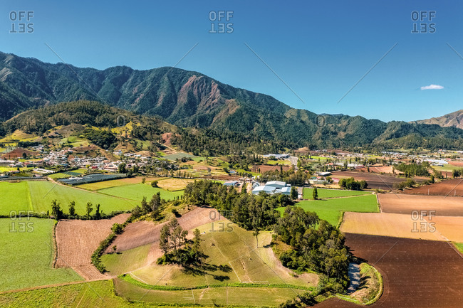 Aerial view of large mountains and agriculture under a clear sky in the constanza valley, la vega, Dominican Republic