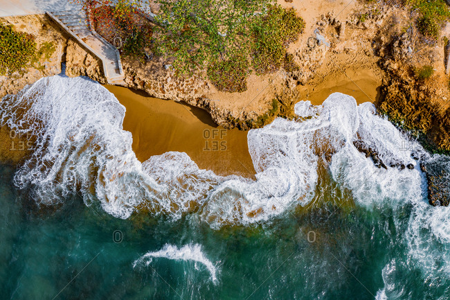 Aerial view of the sea with beautiful waves touching the rocks on a sunny morning on the Malecon in Santo Domingo, Dominican Republic