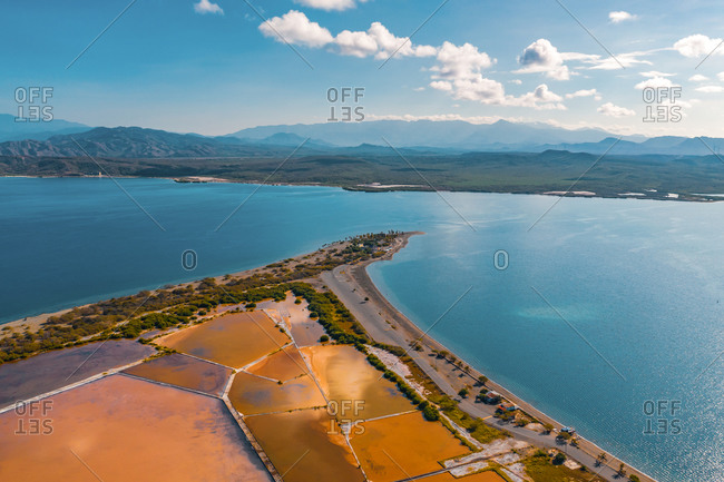 Aerial view of the colorful salt mines on Salinas beach with beautiful mountains on the other side of the bay, Bani, Dominican Republic