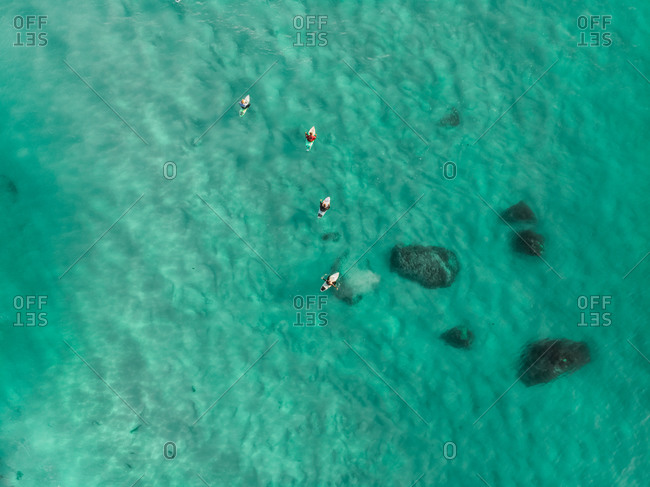 Aerial view of surfers in clear Atlantic Ocean at Camps Bay beach, Cape Town, South Africa.