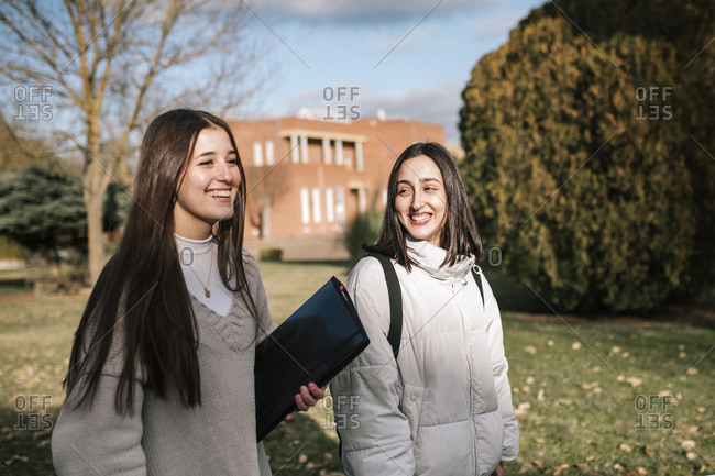 Two student girls walking through the university campus.