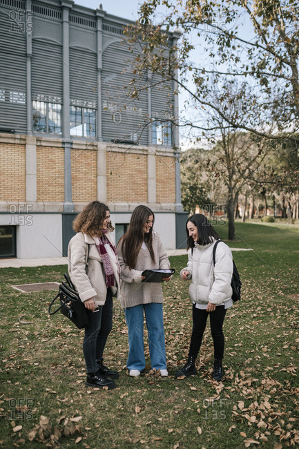 Three college students sharing notes on campus