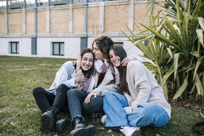 Three Caucasian female friends hugging on the lawn of a college campus