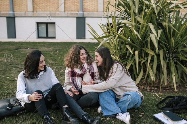 Three Caucasian female friends on the lawn of a college campus