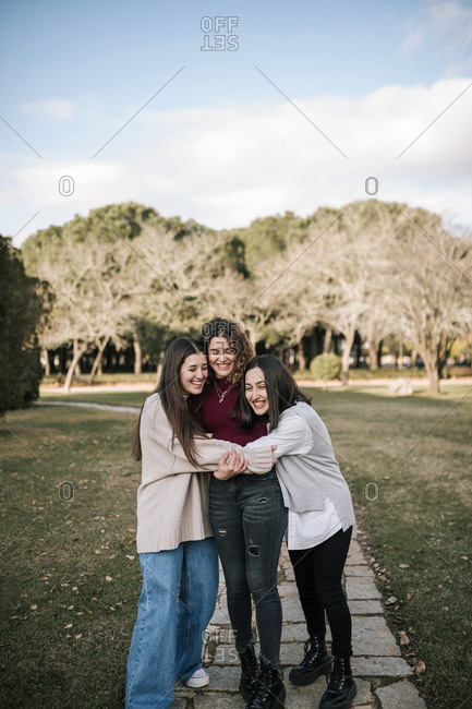 Three Caucasian female friends hugging on a college campus