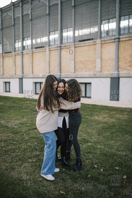 Three Caucasian female friends hugging on a college campus