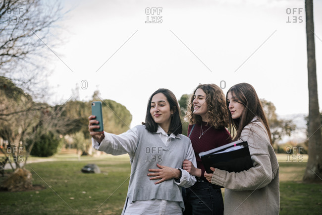 College friends taking a selfie on the campus of a university in Europe