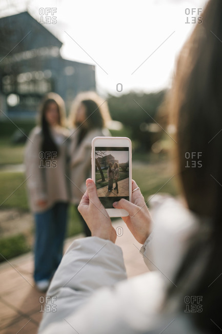 Young woman taking a picture of her two friends on the university campus