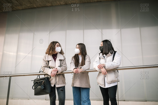 Three female college friends with masks at college