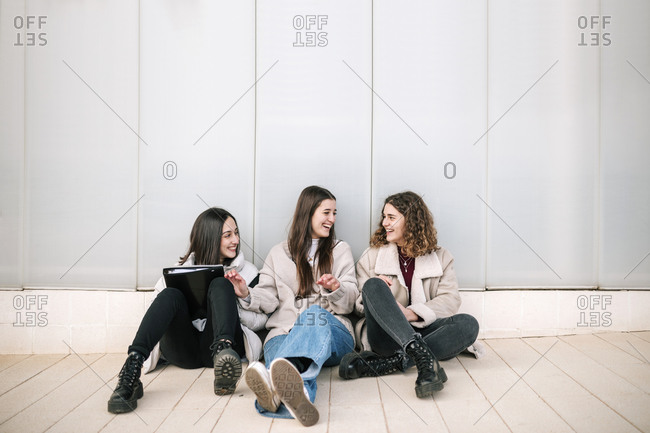 Three female student friends sitting together on the floor of a building at the university