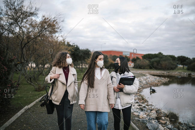 Three friends with masks walking on the campus of the university
