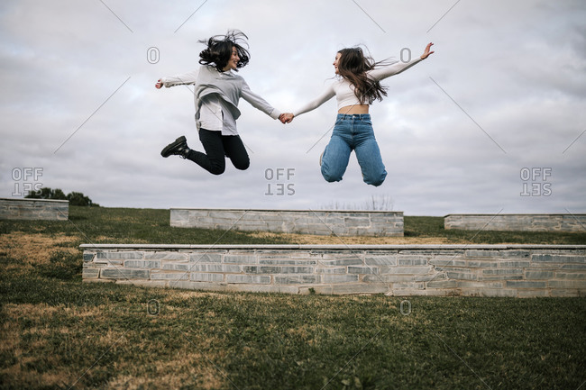Two happy young female friends jumping in the air on a college campus