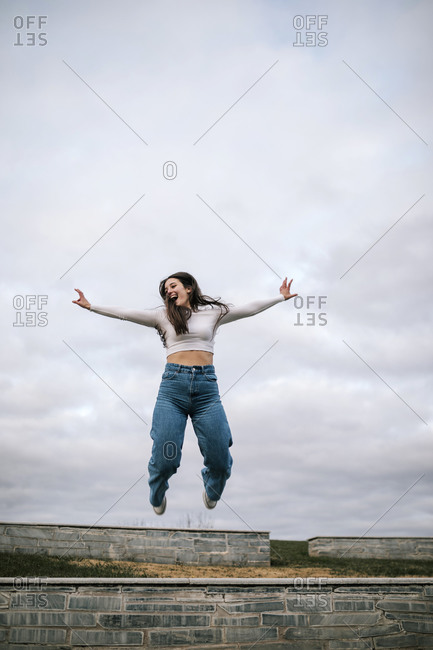 Young woman jumping in the air on a college campus