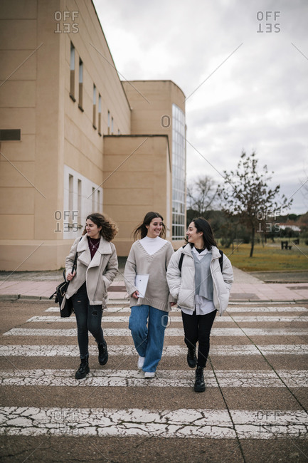 Three female students crossing a zebra crossing on a university campus