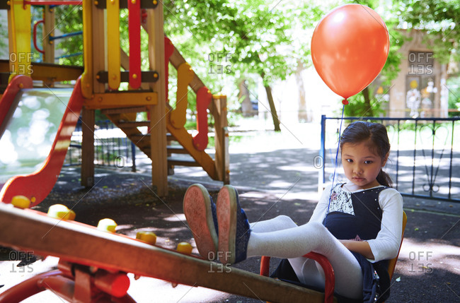 A little girl is holding a red balloon at a playground