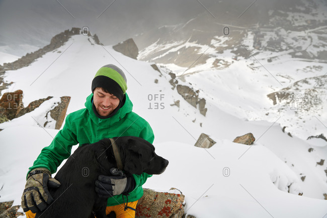 Young man with his black dog on mountain peak