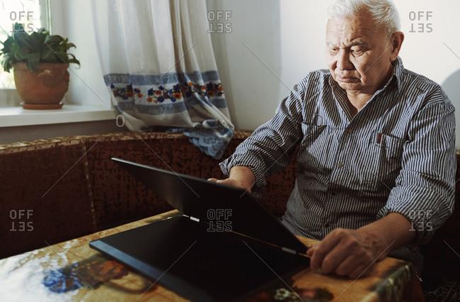 Senior adult man using laptop