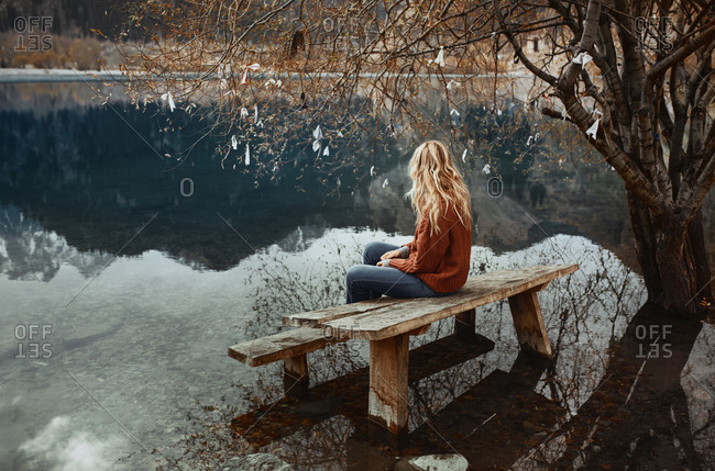 Woman sitting on the bench at the mountain lake and fortune wishing tree