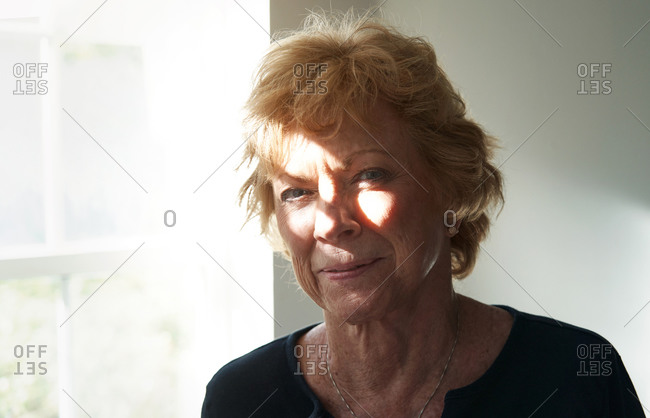 Confident and happy senior woman staying at home