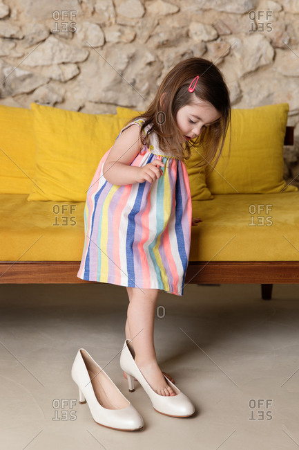 Toddler girl trying on mother's shoes
