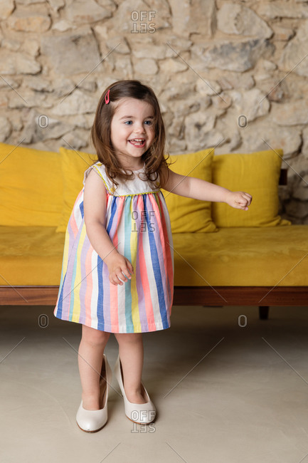 Smiling toddler girl wearing mother's shoes