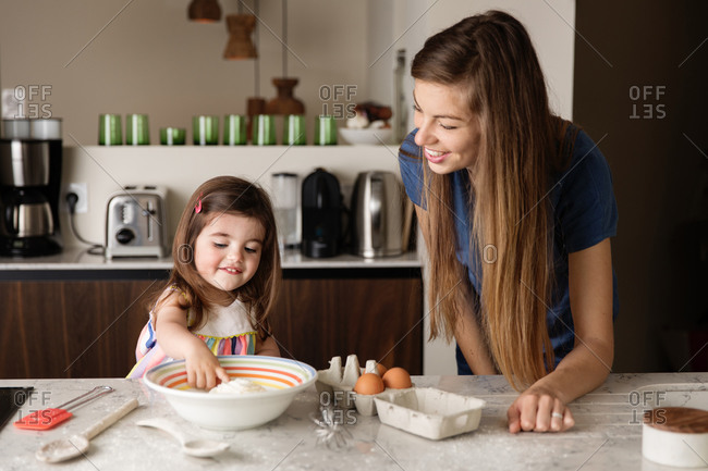 Mother and toddler girl baking together on kitchen counter