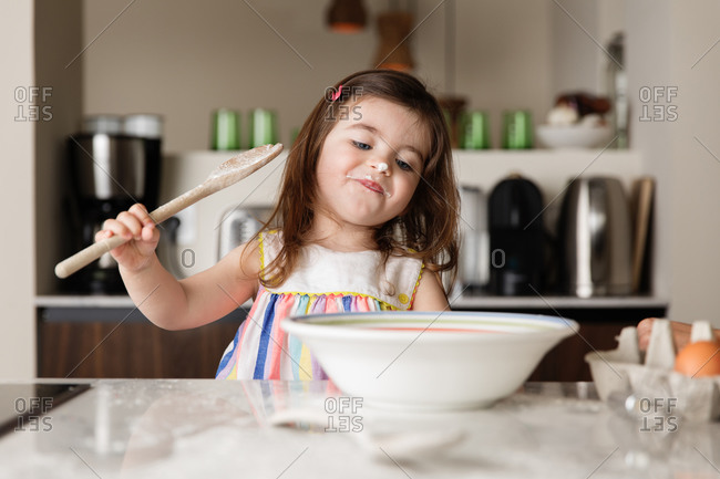 Cute toddler girl preparing food in kitchen
