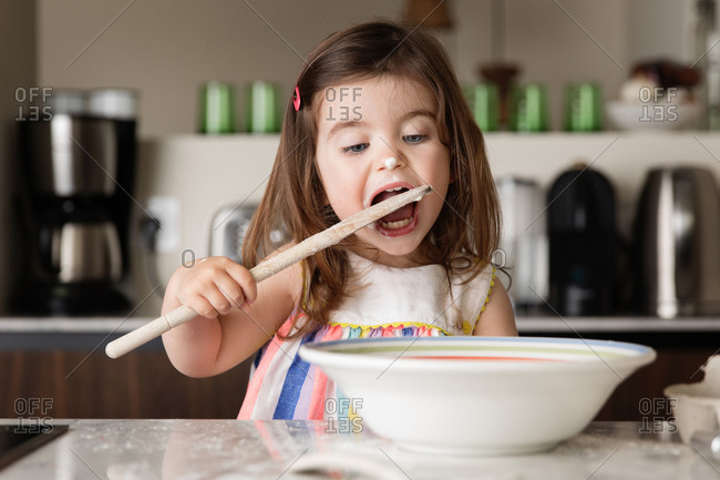 Cute toddler girl tasting food in kitchen
