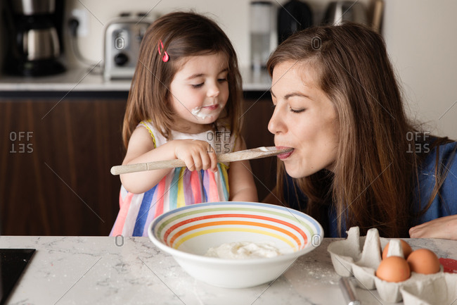 Toddler girl feeding food to mother in kitchen