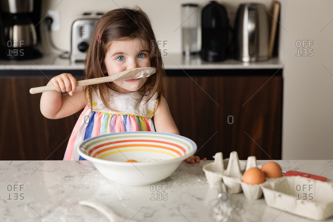 Cute little girl tasting food in kitchen