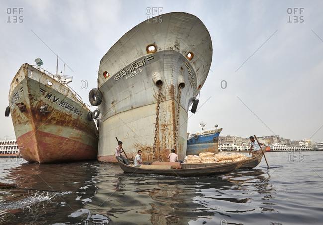 Dhaka, Bangladesh - April 27, 2013: Two cargo boats sailing near three huge ships on the Buriganga River