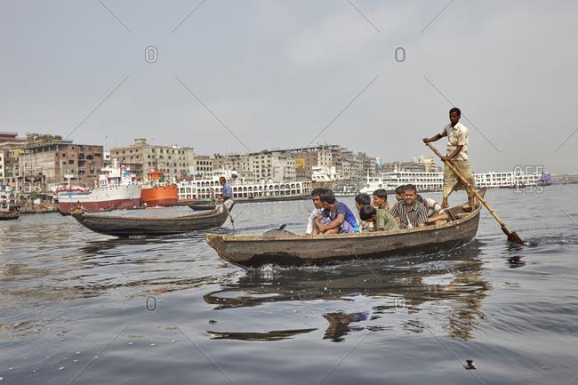 Dhaka, Bangladesh - April 27, 2013: A man navigating his canoe with passengers on the Buriganga River