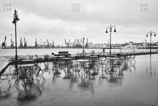 View of a deserted cafe on a cloudy, rainy day with view of the port of Varna, Bulgaria