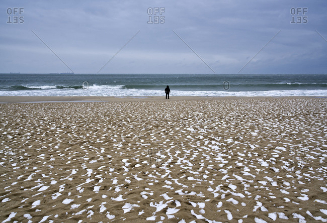 Unrecognizable person walking on frozen beach covered with snow in wintertime