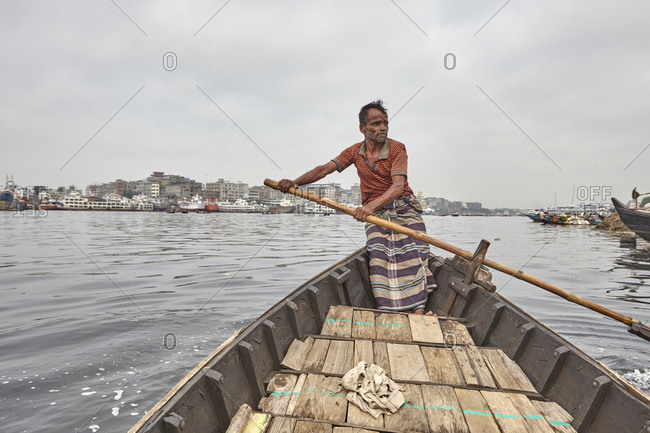 Dhaka, Bangladesh - April 27, 2013: A man navigating his canoe on the Buriganga River